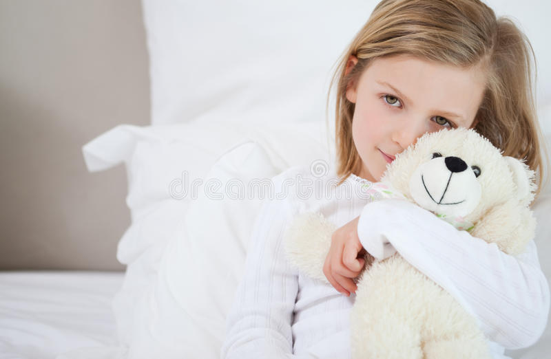 Flicka med henne nalle som sitter på underlaget arkivbilder