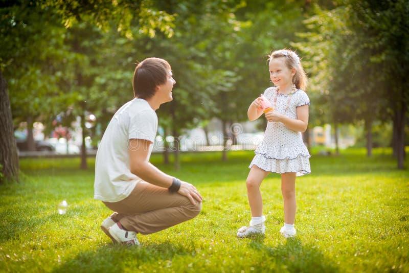 Flicka med hennes fader i parkera royaltyfri foto