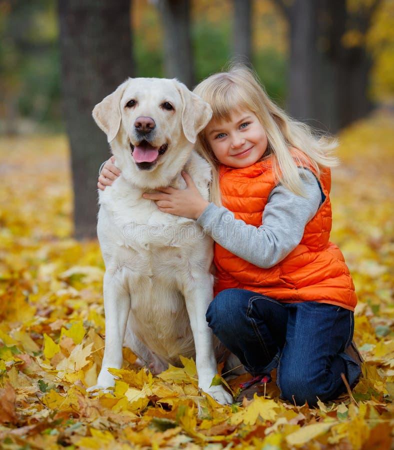Flicka med hennes hund labrador royaltyfri foto