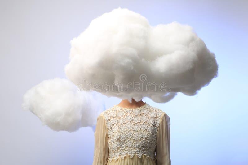Flicka med hennes huvud i molnen royaltyfria bilder