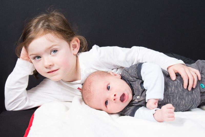 Flicka med hennes lilla broder som ligger spela barn på golv på svart arkivbilder