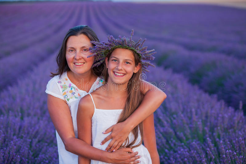 Flicka med hennes moder i lavendelsommarfält fotografering för bildbyråer