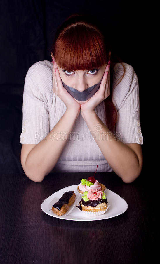 Flicka med hennes mun som förseglas med tejpen och kakor arkivbilder