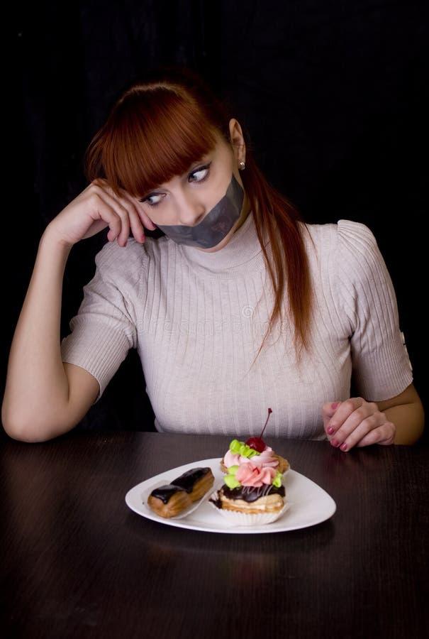 Flicka med hennes mun som förseglas med tejpen och kakor royaltyfri foto