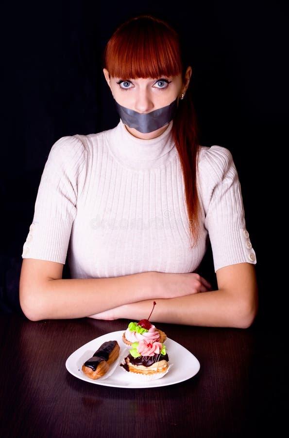 Flicka med hennes mun som förseglas med tejpen och kakor arkivfoton