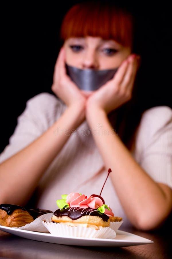 Flicka med hennes mun som förseglas med tejpen och kakor arkivbild