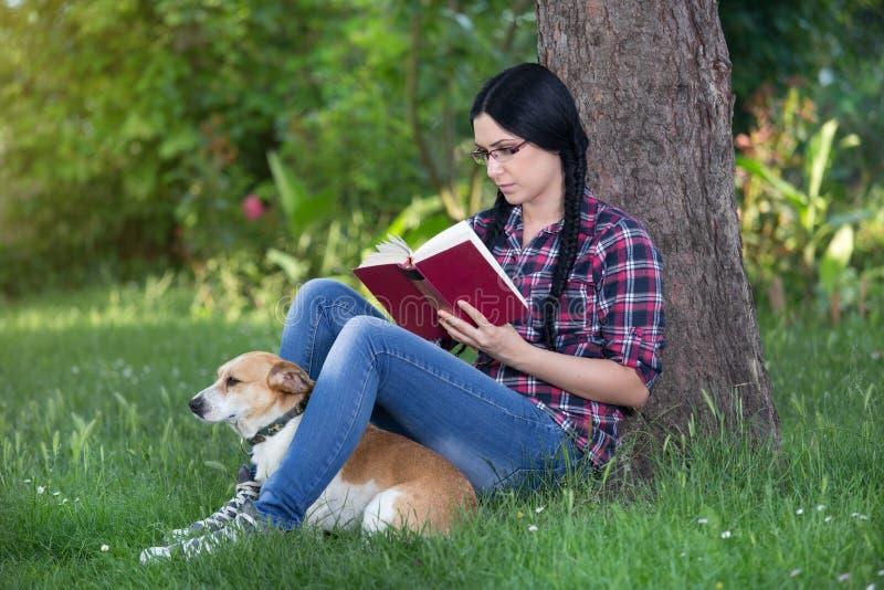Flicka med hunden på gräs som läser en bok arkivbilder