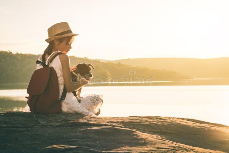 Flicka med hundsammanträde vid en sjö arkivfoto