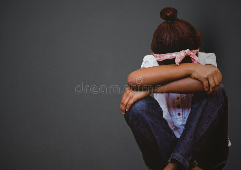 Flicka med huvudet mellan knä mot den gråa väggen fotografering för bildbyråer