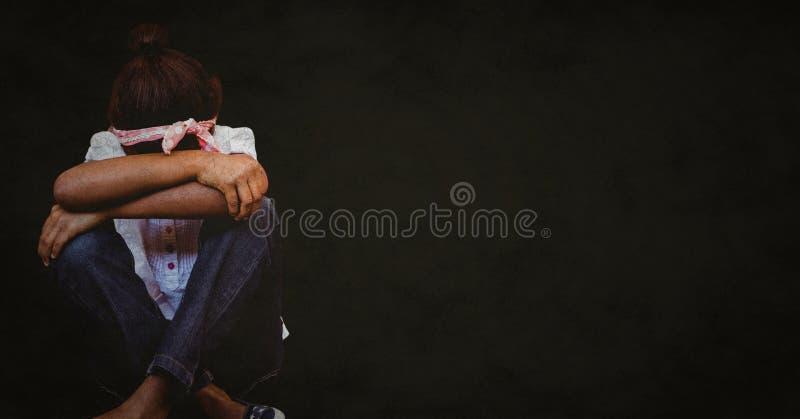 Flicka med huvudet mellan knä mot svart bakgrund med grungesamkopieringen royaltyfria foton