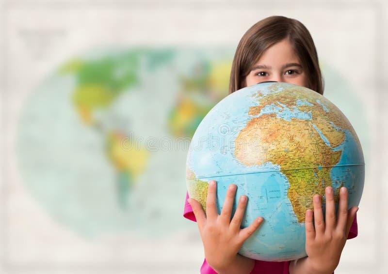 Flicka med jordklotet mot oskarp översikt fotografering för bildbyråer