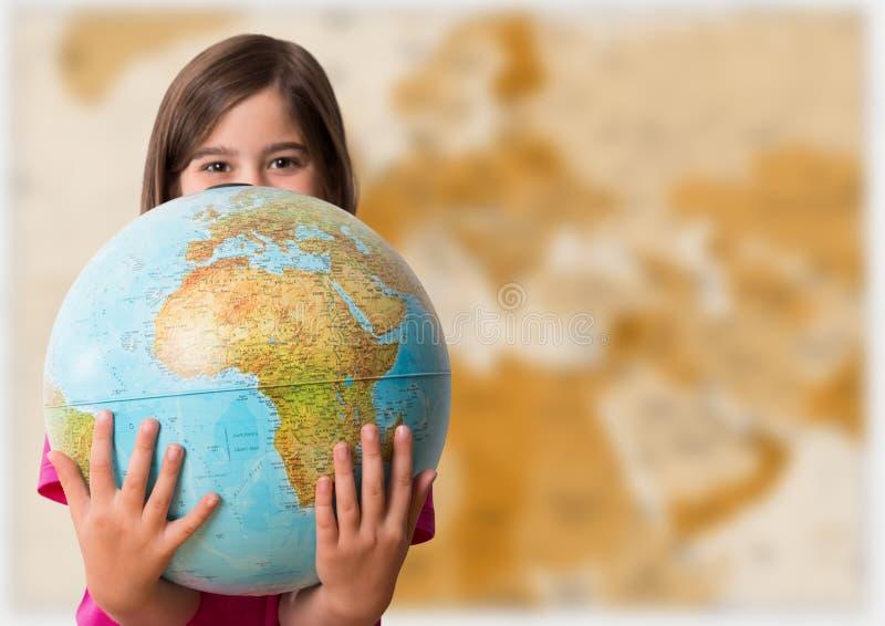 Flicka med jordklotet mot oskarp brun översikt royaltyfri fotografi