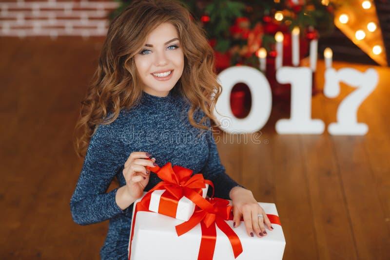 Flicka med julgåvan nära den härliga klädda julgranen royaltyfria bilder