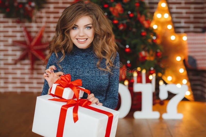 Flicka med julgåvan nära den härliga klädda julgranen royaltyfri foto