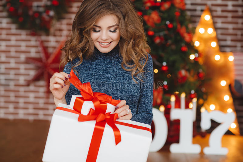 Flicka med julgåvan nära den härliga klädda julgranen royaltyfri fotografi