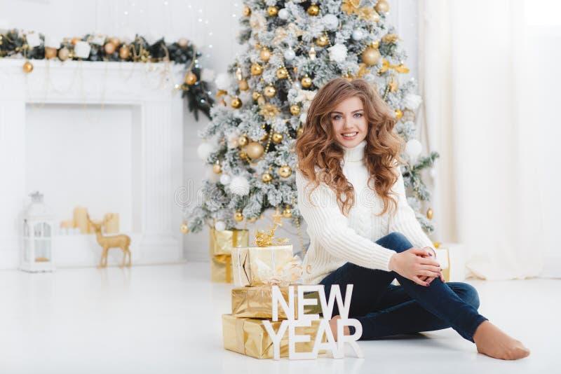 Flicka med julgåvan nära den härliga klädda julgranen arkivbilder