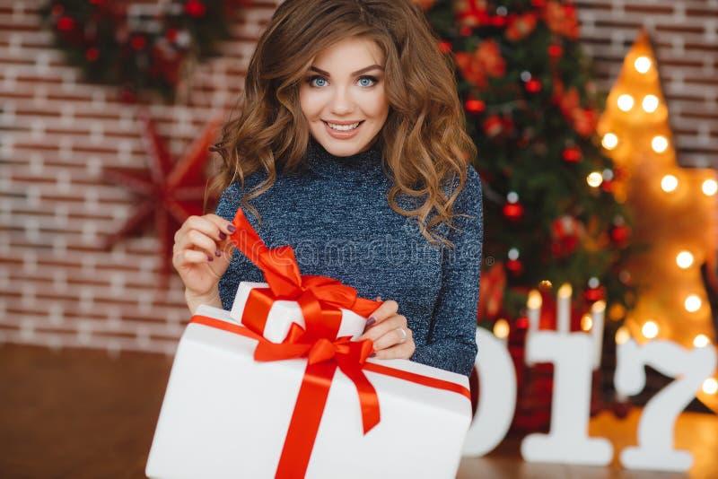 Flicka med julgåvan nära den härliga klädda julgranen royaltyfria foton