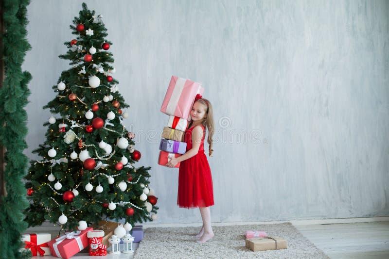 Flicka med julgranen för nytt år för gåvor på gråa gåvor för en bakgrund fotografering för bildbyråer