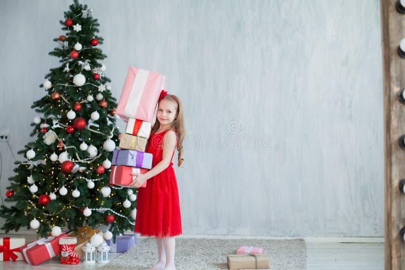 Flicka med julgranen för nytt år för gåvor på gråa gåvor för en bakgrund royaltyfri bild