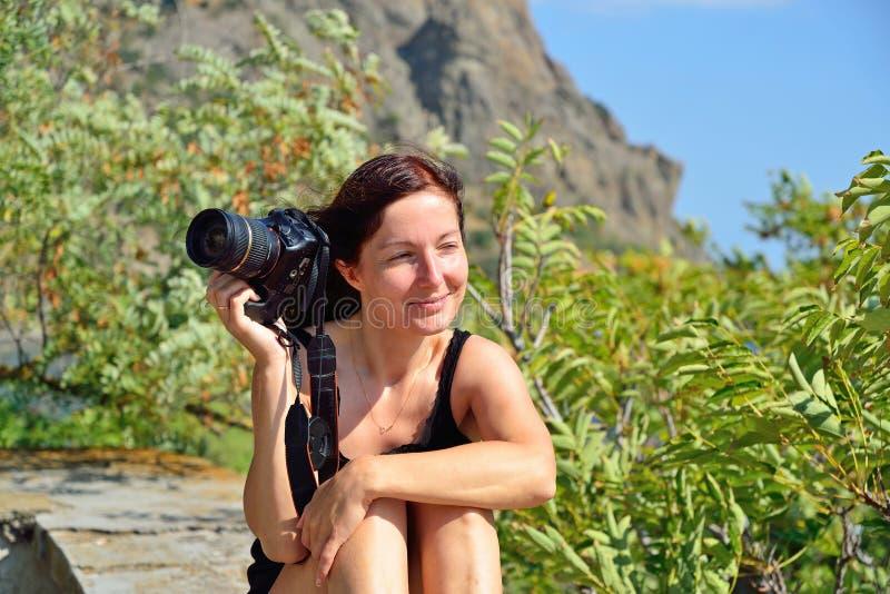 Flicka med kamerasammanträde på balustraden på bakgrunden av fotografering för bildbyråer