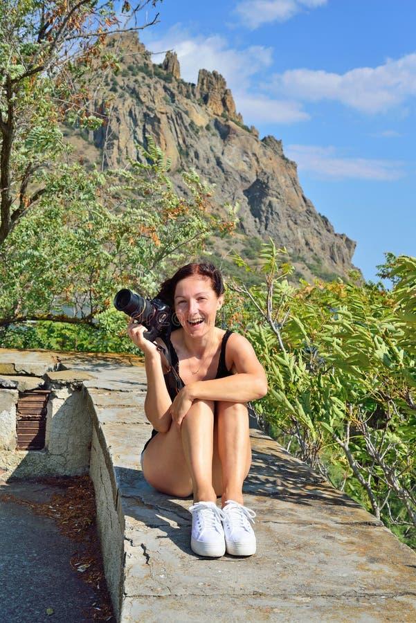 Flicka med kamerasammanträde på balustraden på bakgrunden av royaltyfri foto