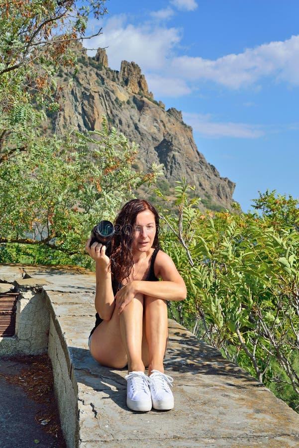 Flicka med kamerasammanträde på balustraden på bakgrunden av arkivbilder