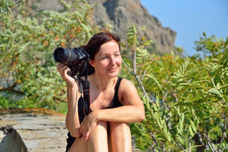 Flicka med kamerasammanträde på balustraden på bakgrunden av royaltyfria bilder