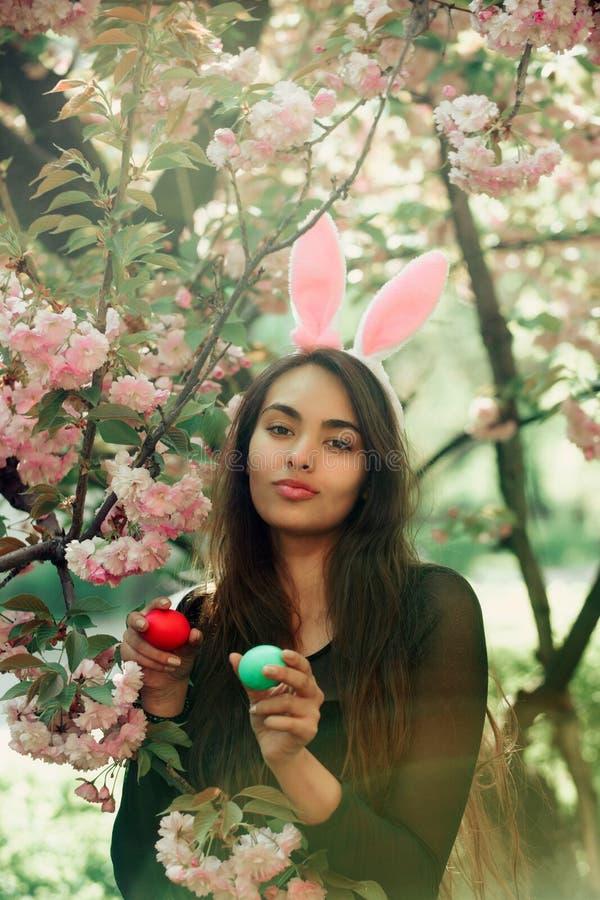 Flicka med kanin?ron som ler med kul?ra ?gg, sakura royaltyfri bild