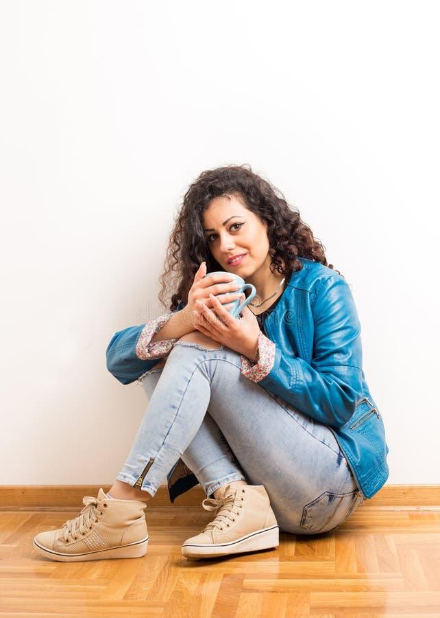 Flicka med koppen som framme sitter av väggen arkivbild