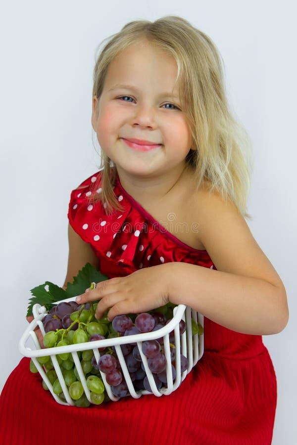 Flicka med korgen av druvor royaltyfri foto