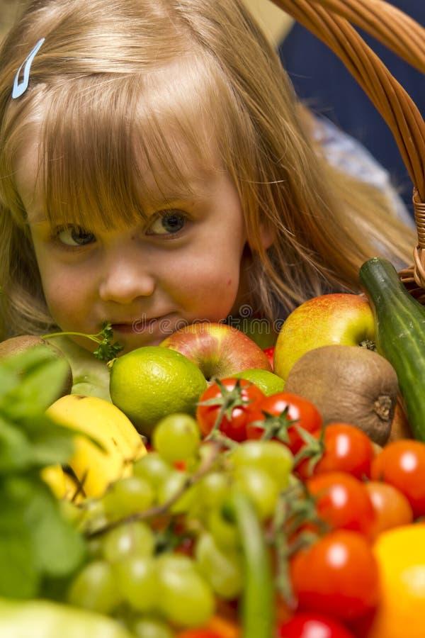 Flicka med korgen av frukt och grönsaker fotografering för bildbyråer