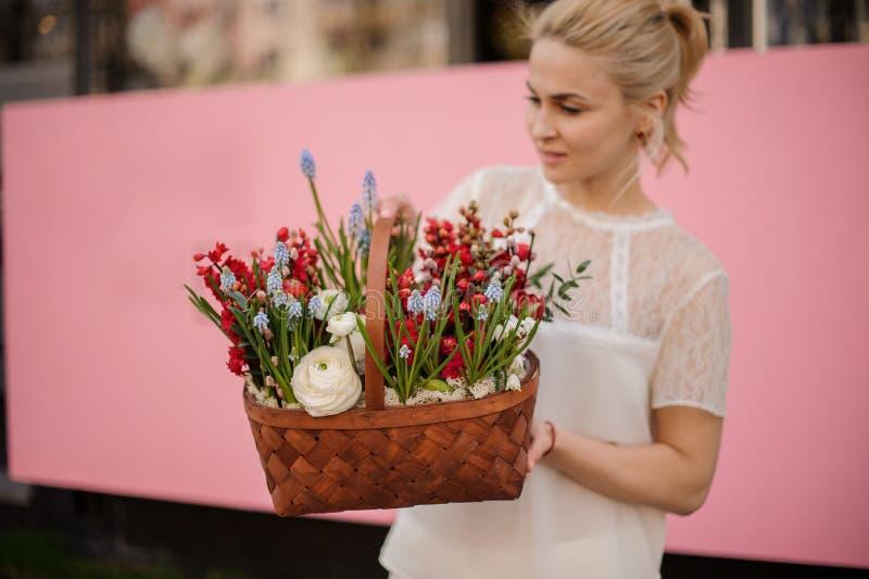 Flicka med korgen av röda och blåa blommor arkivbild