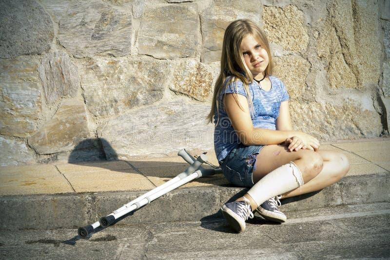 Flicka med kryckor arkivbild