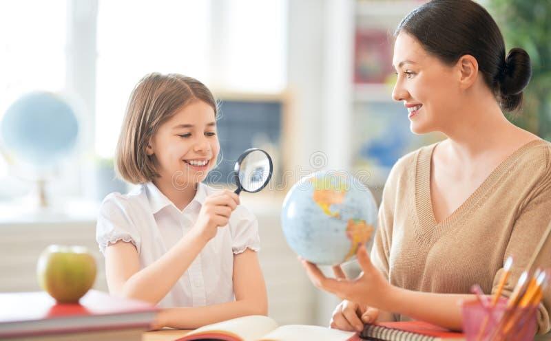 Flicka med läraren i klassrum arkivfoto