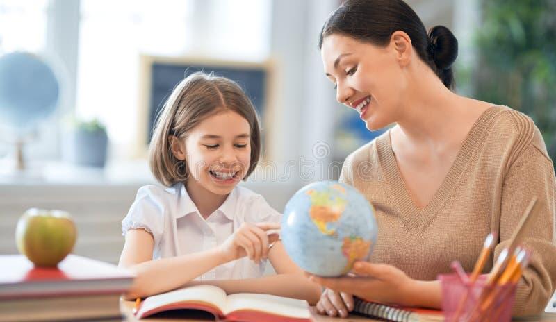 Flicka med läraren i klassrum arkivfoton