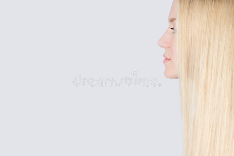 Flicka med långt blont hår som isoleras på vit bakgrund royaltyfria bilder