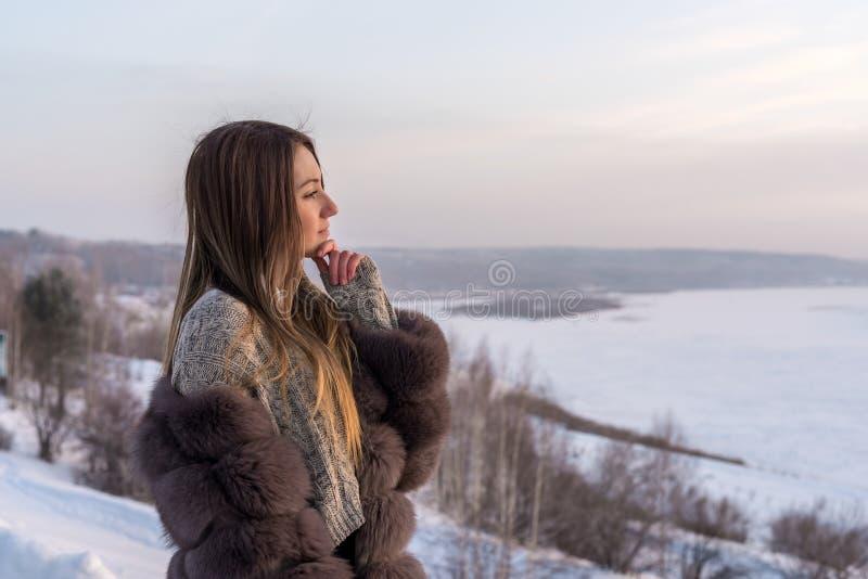 Flicka med långt hår i ett pälslag mot bakgrunden av en vinterdal royaltyfria foton