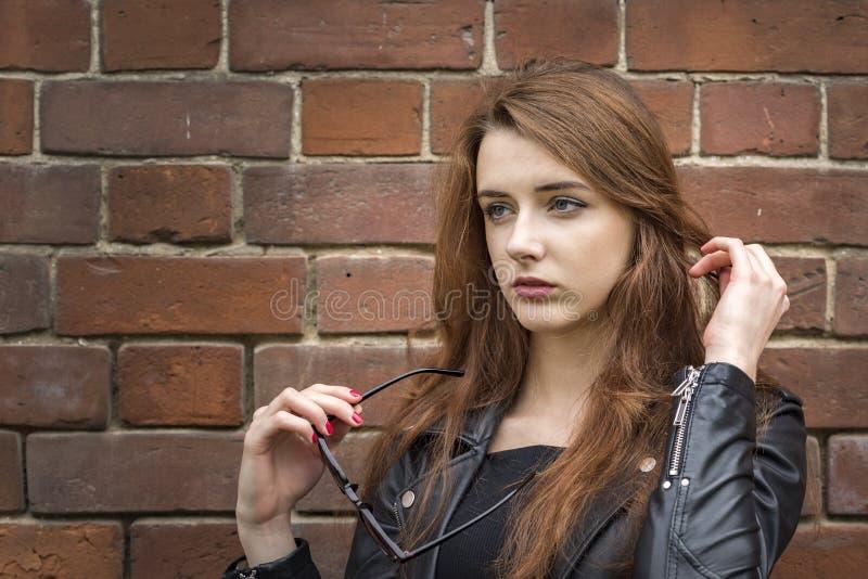 Flicka med långt hår nära en gammal tegelstenvägg royaltyfri bild