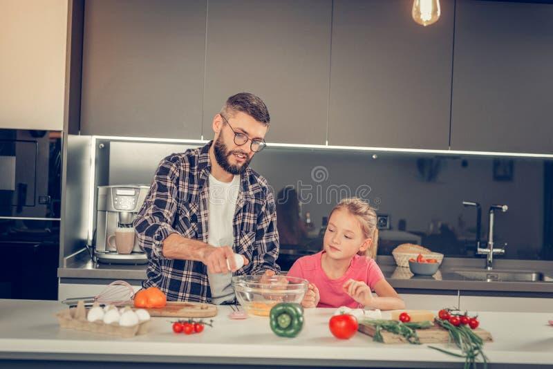 Flicka med långt hår och hennes skäggiga fadern som ser allvarliga royaltyfri fotografi