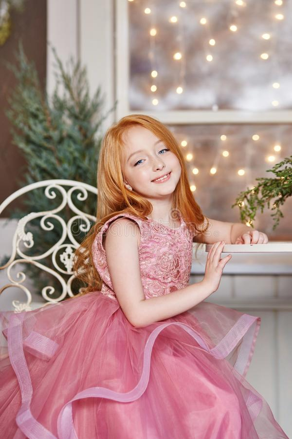Flicka med långt rött hår i en rosa klänning som sitter på tabellen Karnevalferiefödelsedag Stående av en gladlynt rödhårig flick royaltyfri bild