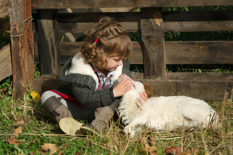 Flicka med lammet på lantgården royaltyfri fotografi