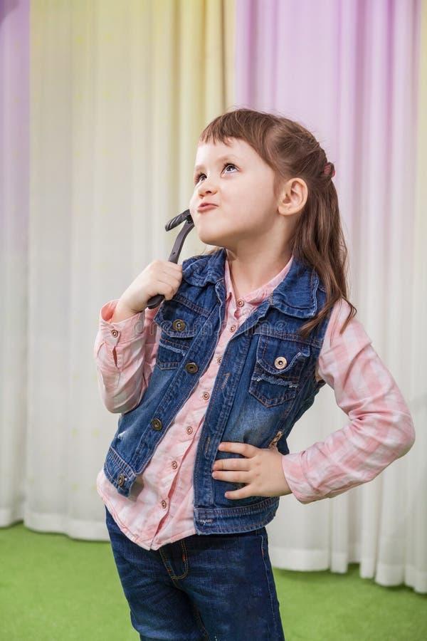 Flicka med leksakmustaschen arkivbild