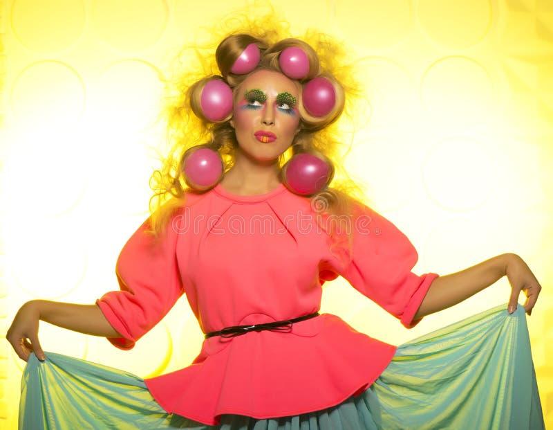 Flicka med ljusa makeup- och hårbollar på gul bakgrund royaltyfria foton
