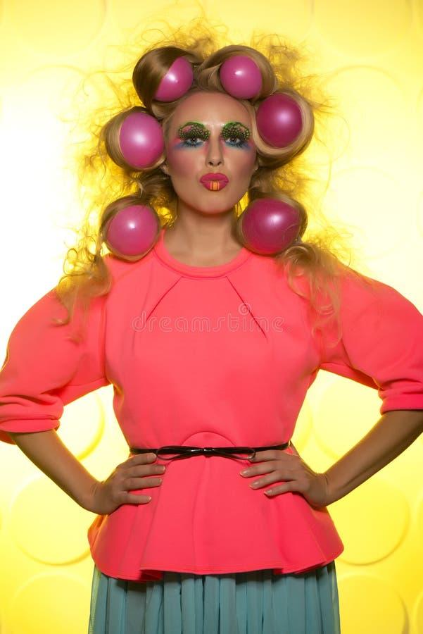 Flicka med ljusa makeup- och hårbollar på gul bakgrund royaltyfria bilder