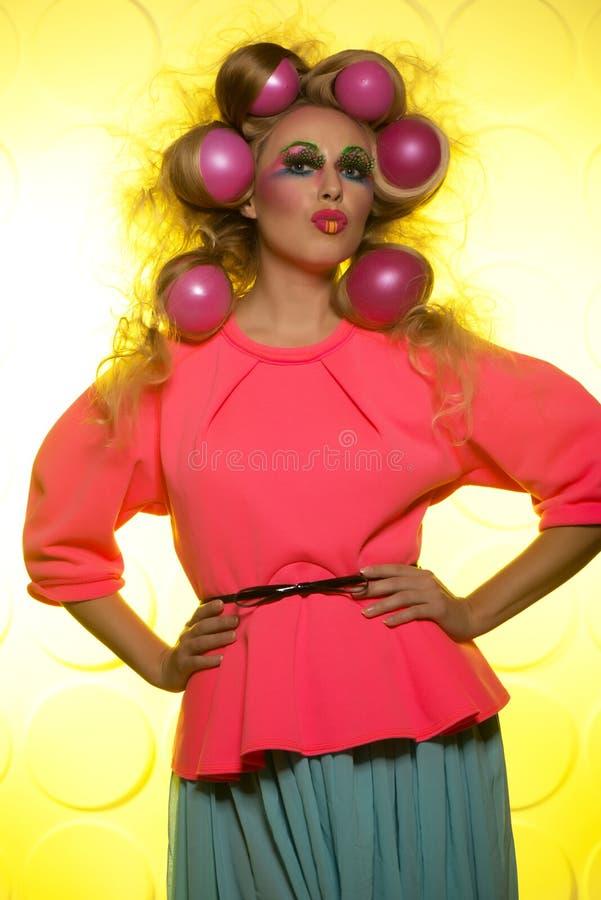 Flicka med ljusa makeup- och hårbollar på gul bakgrund royaltyfri bild