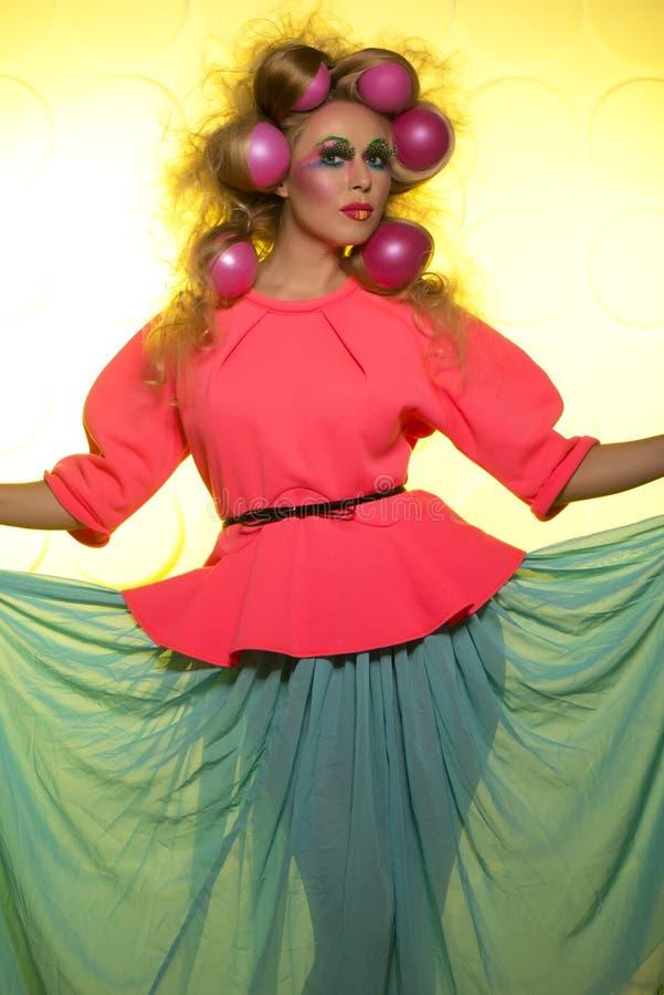 Flicka med ljusa makeup- och hårbollar på gul bakgrund arkivbild