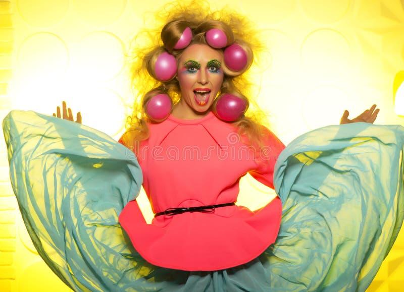 Flicka med ljusa makeup- och hårbollar på gul bakgrund arkivfoton