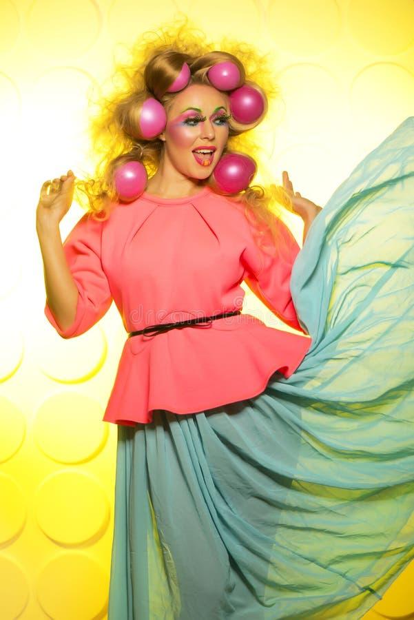 Flicka med ljusa makeup- och hårbollar på gul bakgrund royaltyfri foto