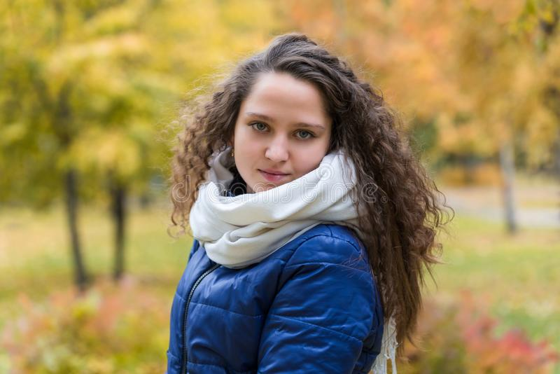 Flicka med lockigt hår mot en bakgrund av höstlövverk arkivfoton