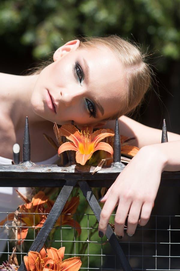 Flicka med makeup p? sund hud med blomman royaltyfri bild